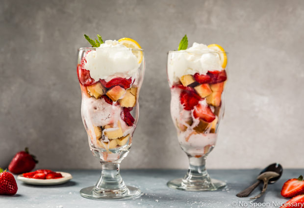 Straight on, landscape shot of a Amaretto Strawberry Shortcake Sundae with another sundae directly next to it and slightly blurred, and spoons, coarse salt, and a small ramekin of sliced strawberries surrounding the sundae glass.