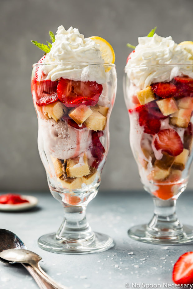 Straight on shot of a Amaretto Strawberry Shortcake Sundae with another sundae directly next to it and spoons, coarse salt, and a small ramekin of sliced strawberries surrounding the sundae.