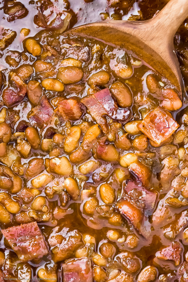 Extreme close-up overhead photo of Bacon Baked Beans being stirred with a wooden spoon.