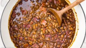 Overhead photo of easy baked beans made with bacon and brown sugar in a large white pot with a wooden spoon stirring the beans.