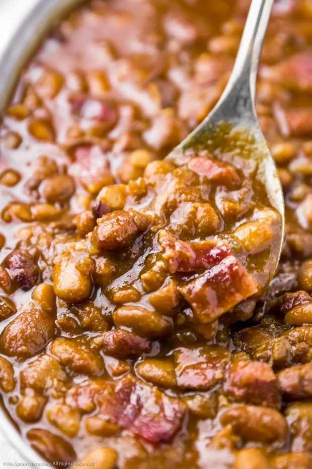 Close-up angled shot of Homemade Bacon & Brown Sugar Barbecue Beans in a galvanized bucket being scooped and served with a spoon.