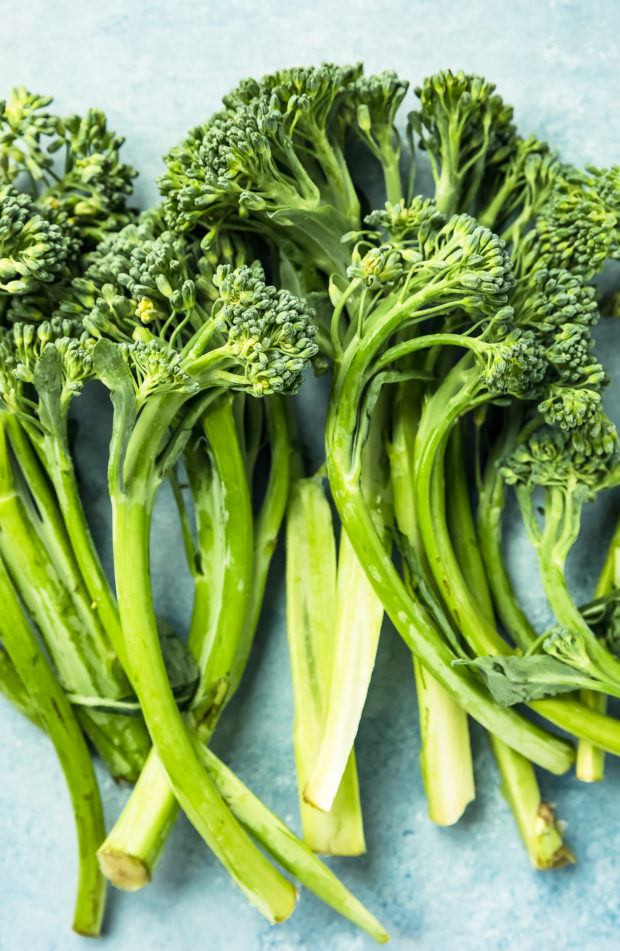 Overhead shot of a few bunches of broccolini on a blue surface - one of the main ingredients in the Creamy Lemon Broccoli Pasta recipe.