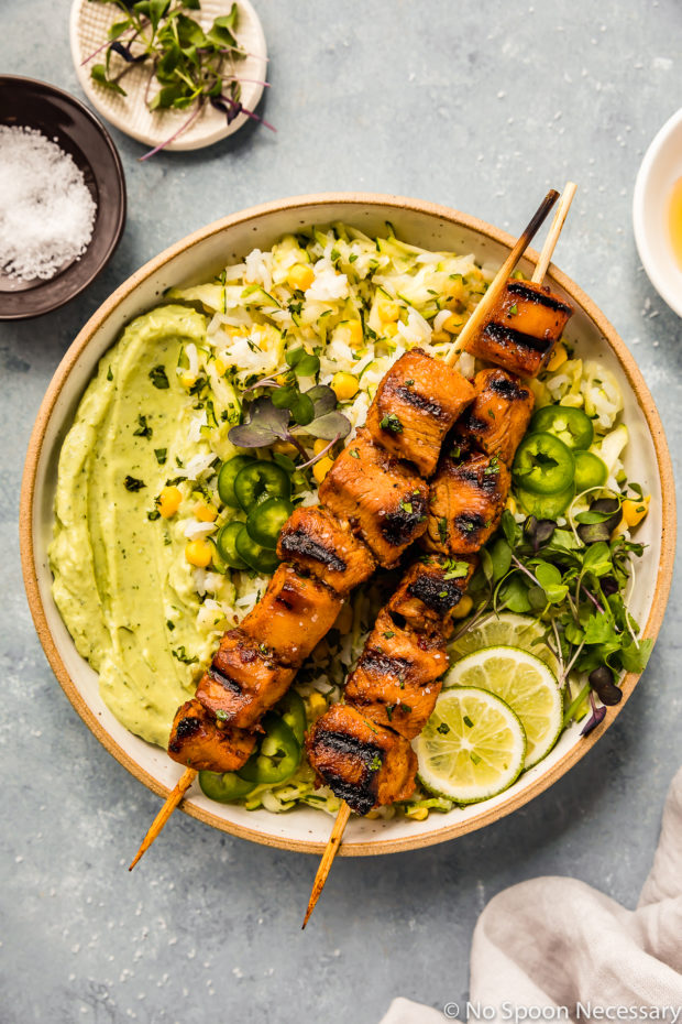 Overhead shot of Grilled Honey Chipotle Chicken Bowls consisting of two grilled chicken skewers, corn studded zucchini rice, avocado cilantro sauce and sliced limes; with a neutral linen and ramekins of salt, microgreens and honey surrounding the bowl.