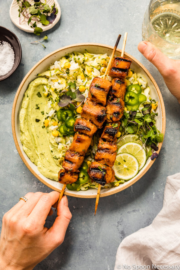 Overhead shot of Grilled Honey Chipotle Chicken Bowls consisting of two grilled chicken skewers, corn studded zucchini rice, avocado cilantro sauce and sliced limes; with a hand holding one of the skewers and another hand holding a glass of wine to the upper right of the bowl.