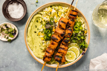 Overhead shot of Grilled Honey Chipotle Chicken Bowls consisting of two grilled chicken skewers, corn studded zucchini rice, avocado cilantro sauce and sliced limes; with a neutral linen, glass of white wine and ramekins of salt and microgreens surrounding the bowl.