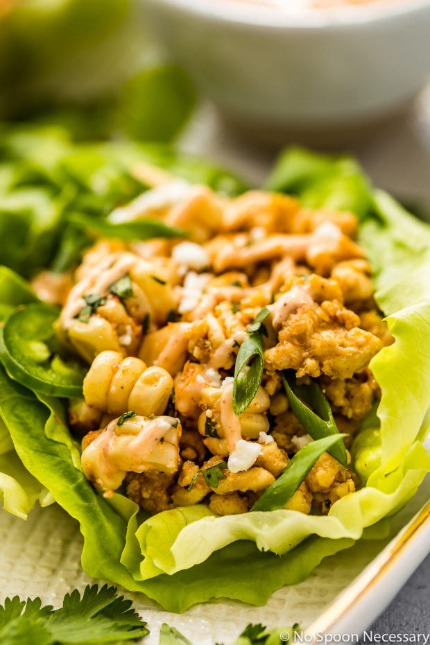 Up close, angled shot of a Mexican Street Corn Lettuce Wrap on a white platter.