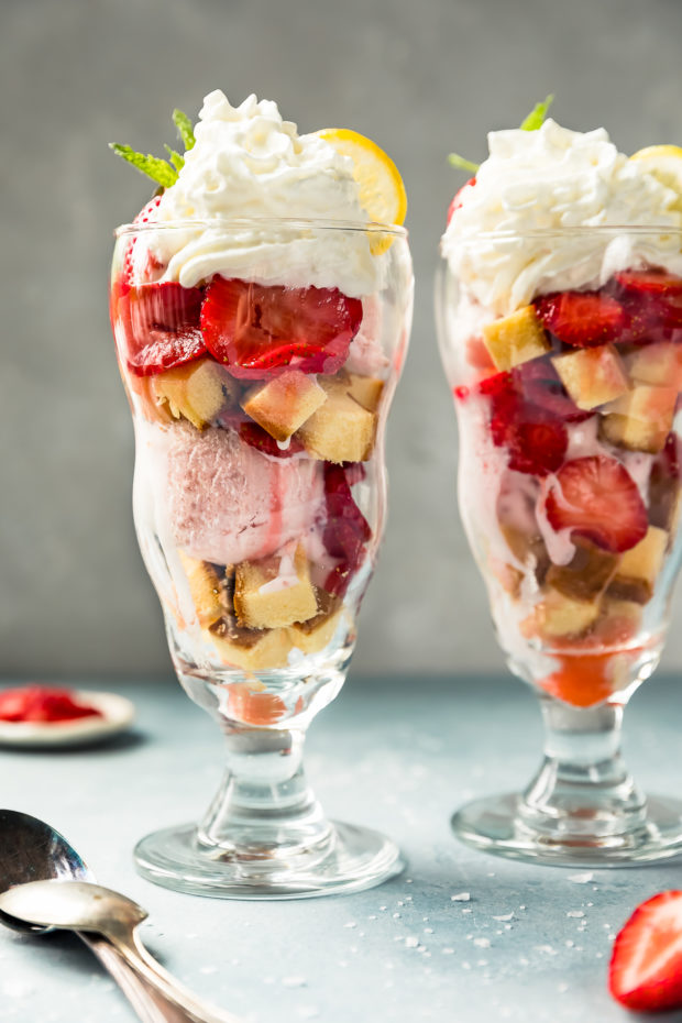 Straight on shot of two homemade Strawberry Shortcake Ice Cream Sundaes with spoons, coarse salt, and a small ramekin of sliced strawberries arranged next to the sundaes.