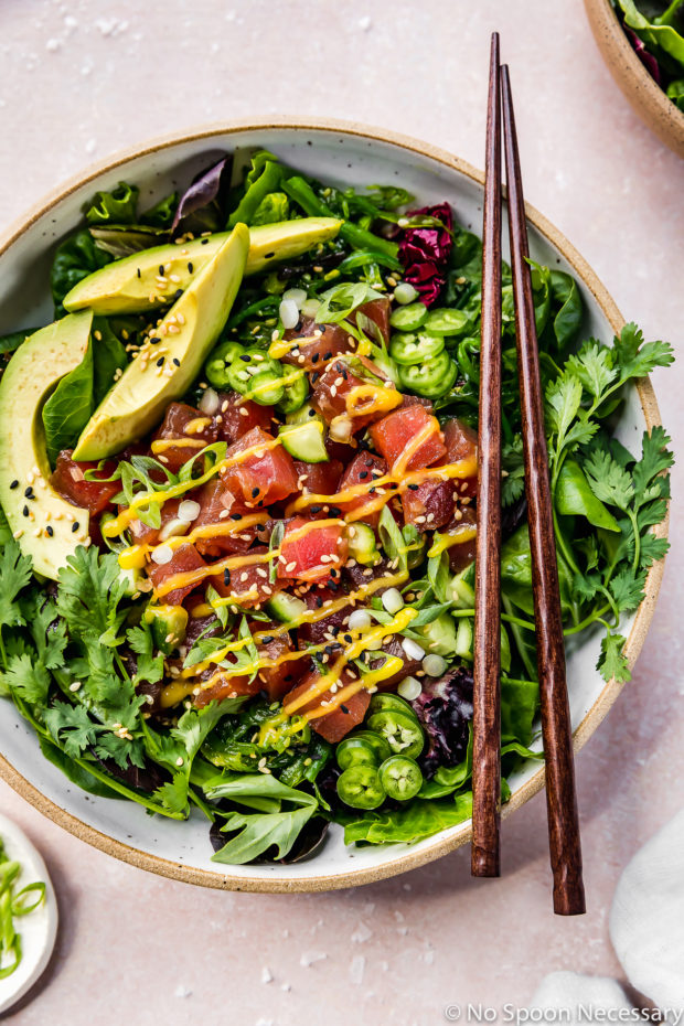 Overhead shot of an Avocado Mango Tuna Poke Salad Bowl with wood chopsticks resting on top of the bowl and an additional bowl and ramekin of sliced scallions surrounding the bowl and barely visible in the shot.