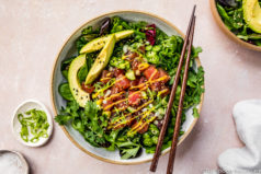 Overhead shot of an Avocado Mango Tuna Poke Salad Bowl with wood chopsticks resting on top of the bowl and an additional bowl and ramekins of sliced scallions and sea salt surrounding the bowl and barely visible in the shot.