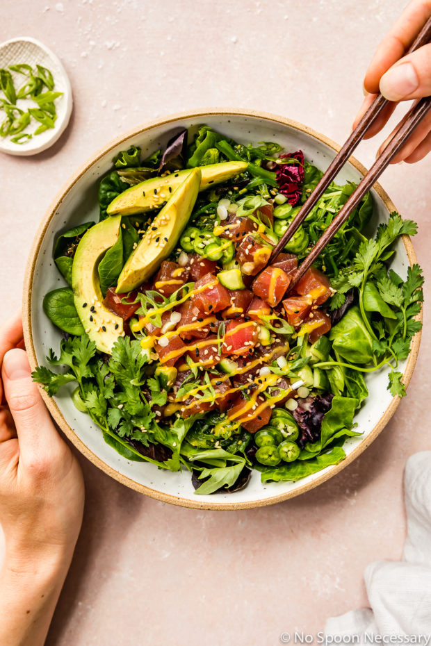 Overhead shot of Avocado Mango Tuna Poke Salad Bowl with a hand holding a chopstick inserted into the salad and another hand holding the bowl.