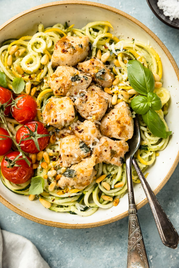 Overhead, close-up photo of Basil Pesto Chicken Pasta garnished with oven roasted tomatoes in a large bowl with two forks tucked under the pasta.