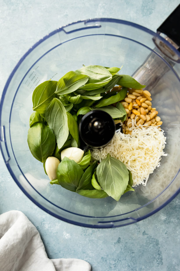 Overhead photo of a food processor bowl filled with all the ingredients needed to make basil pesto. (Process photo of step 2 of the basil pesto chicken recipe.)