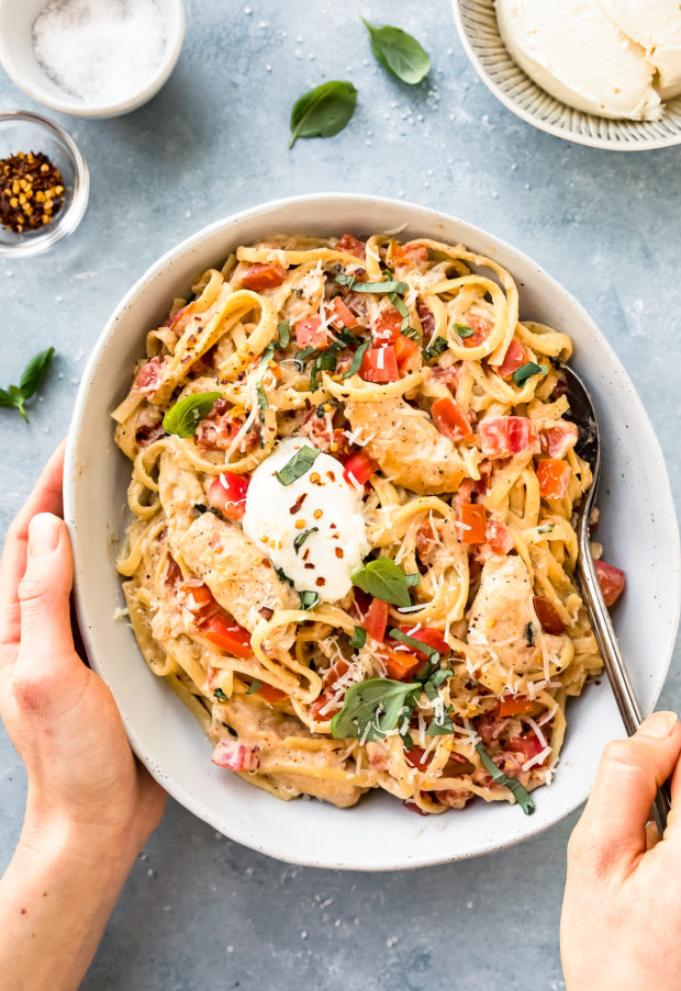 Overhead shot of One Pot Chicken Margherita Pasta in a neutral colored serving bowl with a hand holding the bowl and another hand holding serving spoons inserted into the pasta; with a bowl of ricotta and ramekins of salt and crushed red pepper surrounding the bowl.
