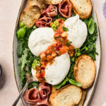 Overhead, landscape shot of a white platter with arugula, burrata, prosciutto, Quick Basil Peach Chutney and toasted slices of baguette with lavender water glass, a ramekin of flaky sea salt and a neutral linen surrounding the platter.