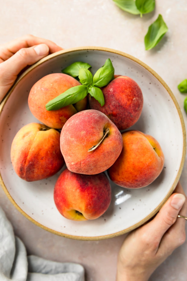 Overhead shot of a neutral bowl filled with fresh peaches and basil leaves with two hands holding the bowl. (A photo of the two main ingredients in the Quick Peach Chutney recipe)