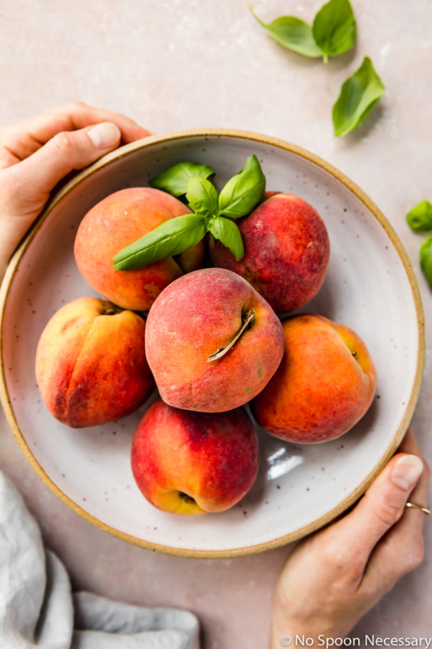 Overhead shot of a neutral bowl filled with fresh peaches and basil leaves with two hands holding the bowl. (A photo of the two main ingredients in the Quick Basil Peach Chutney recipe)