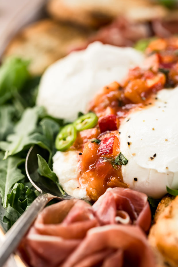 Angled, up-close shot of a white platter with arugula, burrata, prosciutto, Quick Basil Peach Chutney and toasted slices of baguette with the focus of the shot on the chutney.
