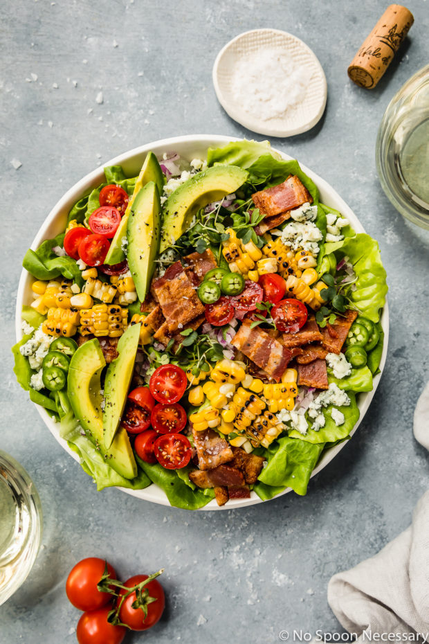 Overhead shot of a Summer Corn BLAT Salad in a white shallow bowl with glasses of white wine, wine cork, vine ripe cherry tomatoes, and ramekin of salt surrounding the bowl.