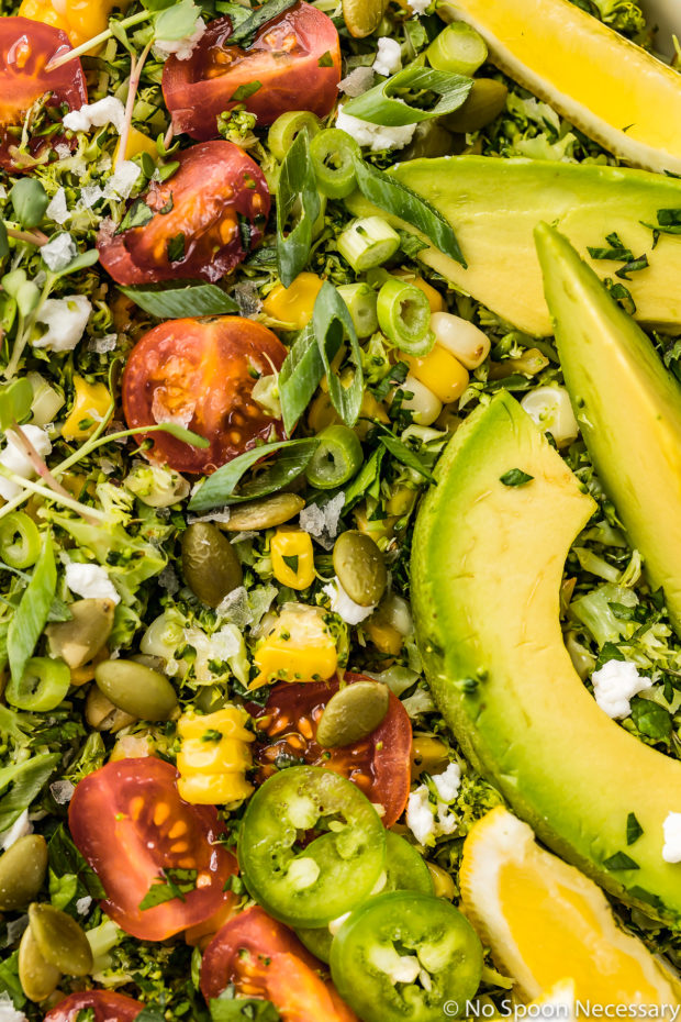 Overhead, up-close shot of Summer Corn & Broccoli Tabbouleh salad and garnished with microgreens, sliced scallions ,avocados and lemon wedges.