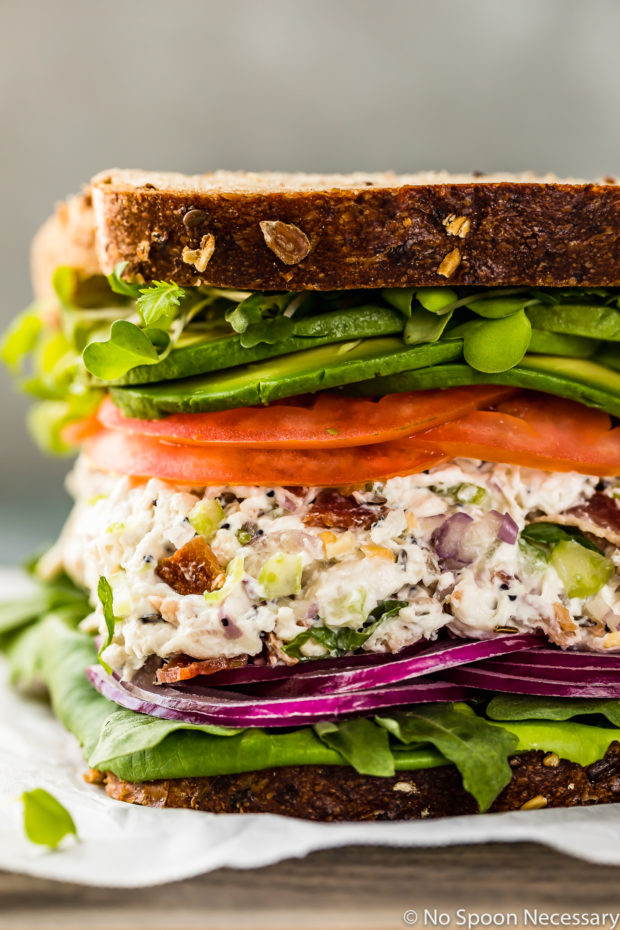 Straight on, up close shot of a Creamy Bacon Everything Spice Chicken Salad Sandwich with lettuce, tomato, avocado and red onions on multigrain bread on a gray wood board lined with a sheet of parchment paper.