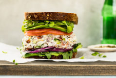 Straight on shot of a Creamy Bacon Everything Spice Chicken Salad Sandwich with lettuce, tomato, avocado and red onions on multigrain bread on a gray wood board with a small ramekin of everything spice and green bottle of water blurred in the background.