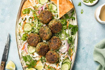 Overhead shot of a platter of Asian Crispy Pan Fried Falafels on a bed of Asian slaw with pita bread; with a pale green linen, knife, lime wedge, ramekin of sliced scallions and small ceramic jar of miso tahini surrounding the platter.