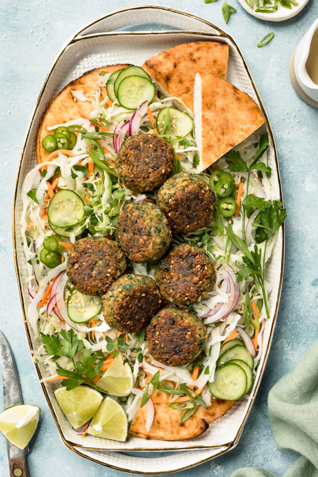 Overhead shot of a platter of Asian Crispy Pan Fried Falafels on a bed of Asian slaw with pita bread; with a knife, lime wedge, ramekin of sliced scallions and small ceramic jar of miso tahini surrounding the platter.