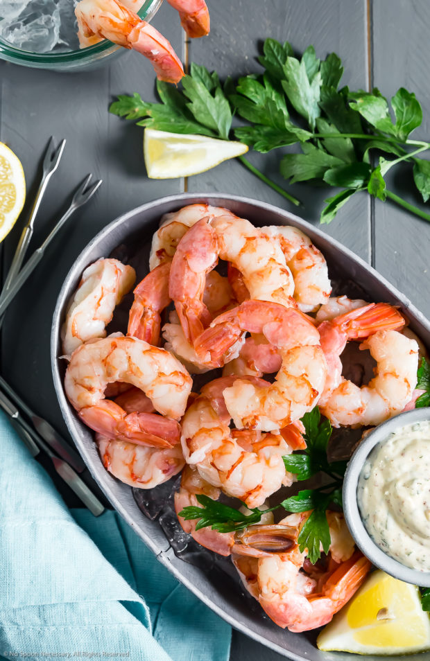 Overhead photo of a small gray serving dish filled with ice and topped with Poached Cocktail Shrimp and a ramekin of Remoulade; with fresh parsley, lemon wedges, a light blue linen and a glass of shrimp cocktail arranged around the dish.