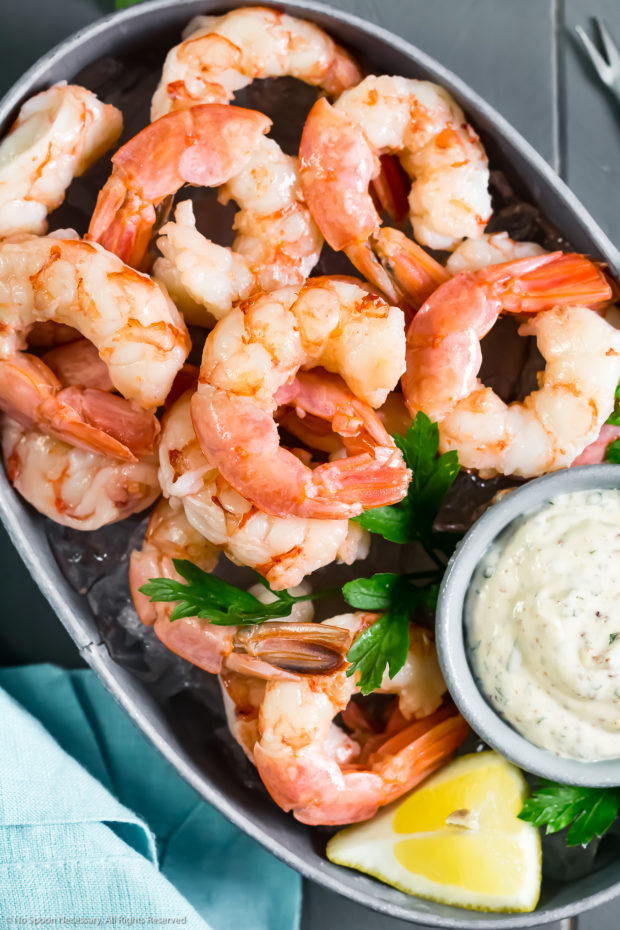 Overhead photo of a small, deep-sided serving bucket filled with ice and topped with Poached Shrimp Cocktail with a small ramekin of homemade remoulade sauce next to the shrimp; with a light blue linen and shrimp fork on either sides of the bucket.