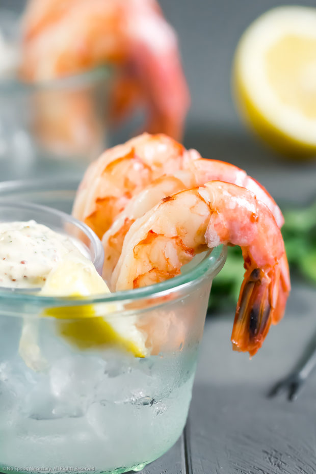 Straight on photo of a small glass bowl filled with ice with Poached Shrimp looped around the edges of the bowl and a small ramekin of Remoulade on top of the ice.