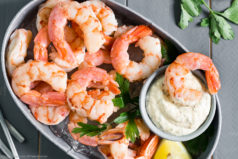 Overhead photo of a small, deep-sided serving bucket filled with ice and topped with Perfect Poached Cocktail Shrimp with a small container of Remoulade sauce next to the shrimp and an individual shrimp dunked into the sauce.