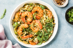 Overhead photo of Healthy Thai Noodles topped with shrimp in a white bowl with ramekins of red pepper flakes and scallions surrounding the bowl.