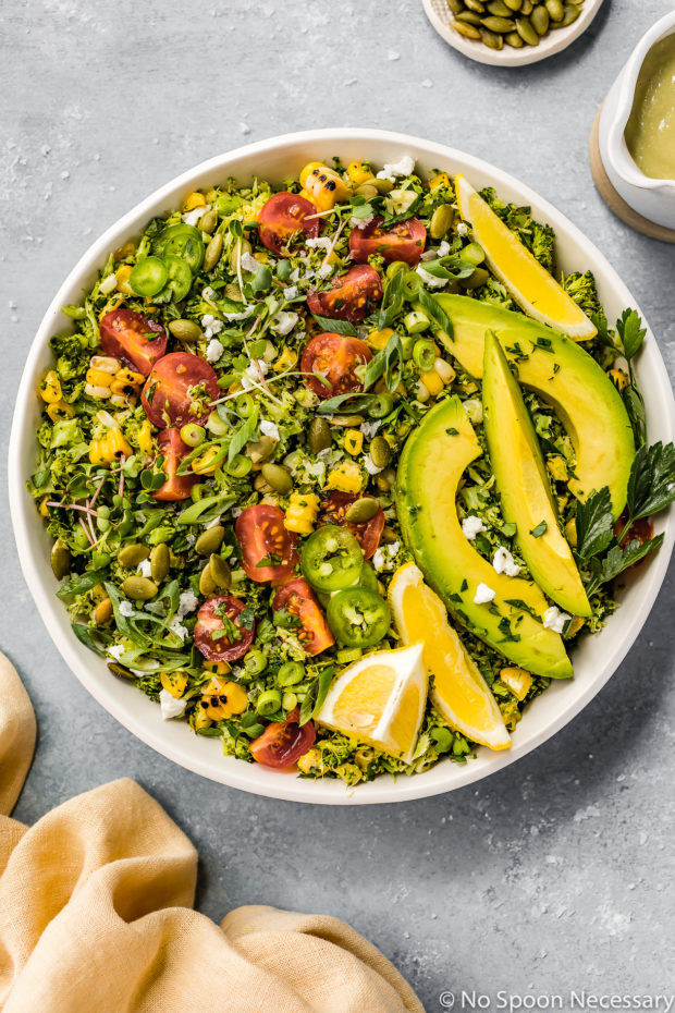 Overhead shot of a white bowl filled with Summer Corn & Broccoli Tabbouleh salad and garnished with sliced avocados and lemon wedges with a pale yellow linen, small ramekin of pepitas and jar of creamy jalapeno hummus dressing surrounding the bowl.