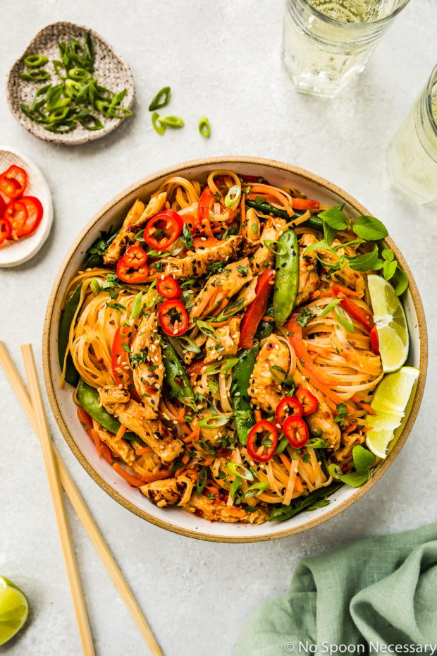 Overhead shot of Thai Spicy Chili Chicken & Noodles in a neutral colored bowl with lime wedges as garnish and a green linen, chopsticks, wine glasses, ramekin of sliced scallions and ramekin of chiles surrounding the bowl.