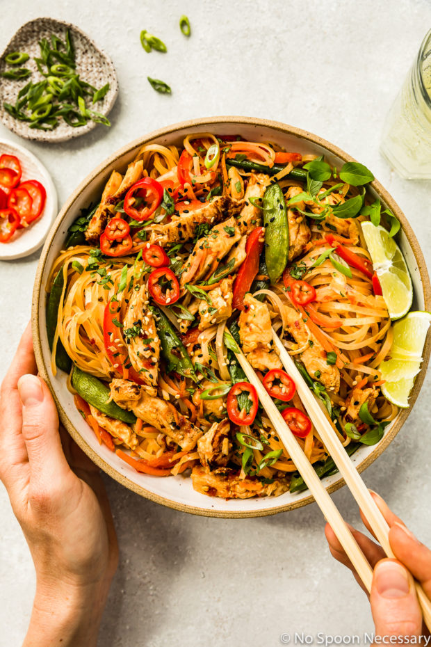 Overhead shot of Thai Spicy Chili Chicken & Noodles in a neutral colored bowl with a hand holding a pair of chopsticks inserted into the noodles and a wine glass, ramekin of sliced scallions and ramekin of chiles arranged above the bowl.