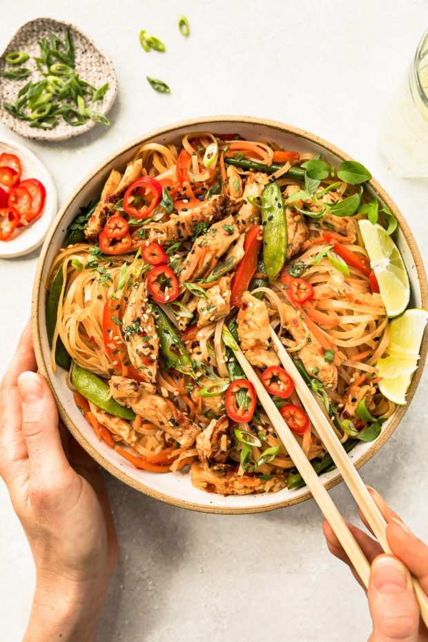 Overhead shot of Chinese Chili Chicken Stir-fry in a neutral colored bowl with a hand holding a pair of chopsticks inserted into the noodles and a wine glass, ramekin of sliced scallions and ramekin of chiles arranged above the bowl.