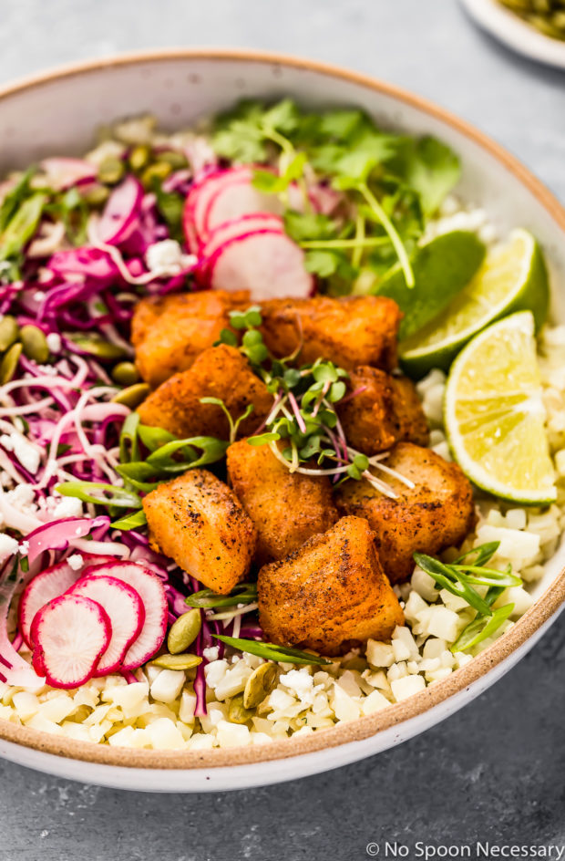 Angled shot of Easy White Fish Taco Bowls on a bed of cauliflower rice and slaw in a neutral bowl with a ramekin of pepitas blurred in the background.