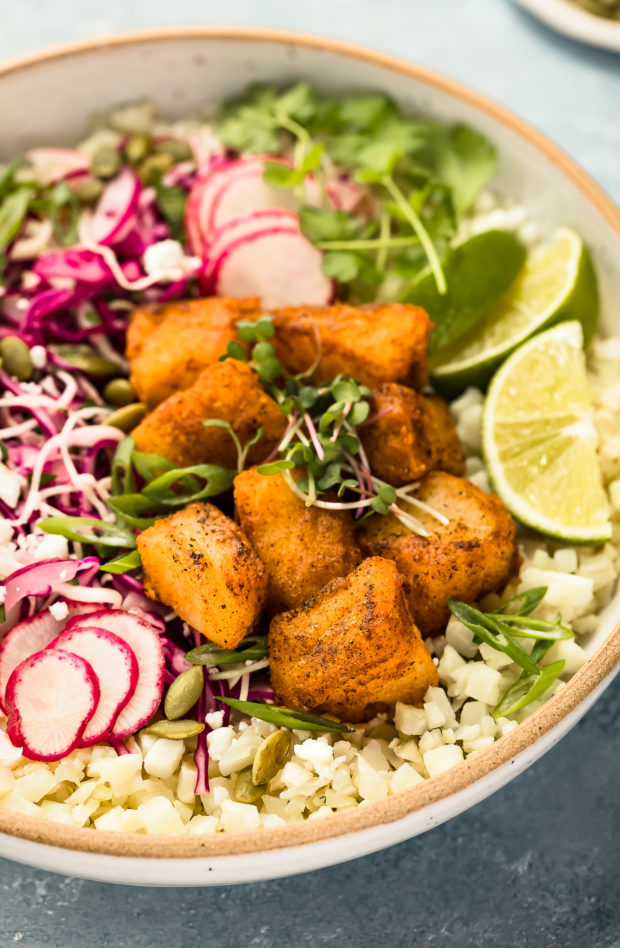 Close-up angled photo of crispy pieces of white fish on a bed of cauliflower rice with fresh slaw in a white bowl.