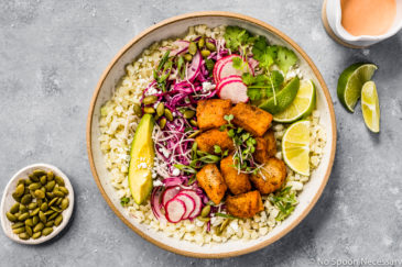 Overhead shot of Easy White Fish Taco Bowls with cauliflower rice and slaw in a neutral bowl with a ramekin of pepitas, lime wedges and a ramekin of sauce surrounding the bowl.