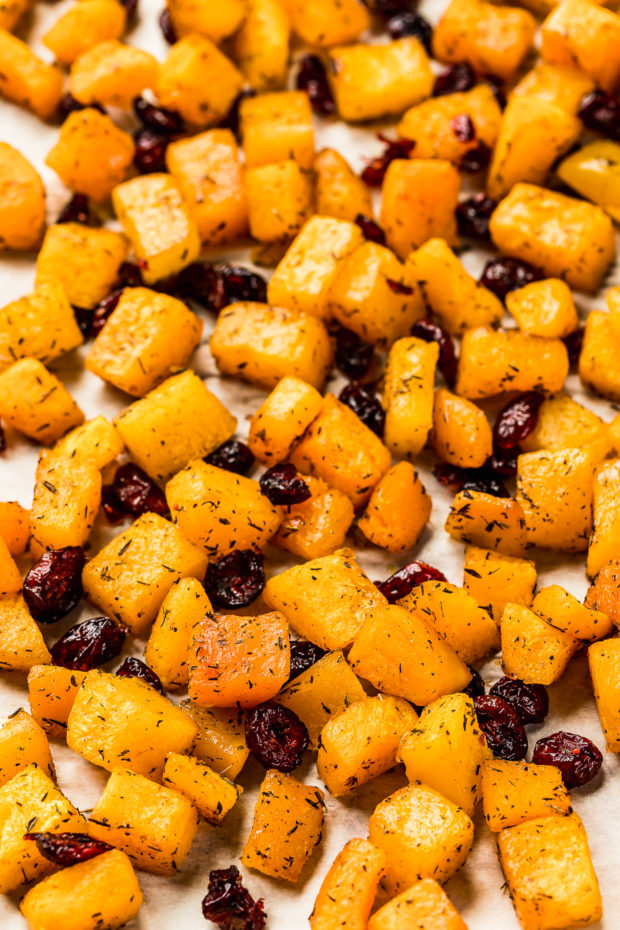 Angled shot of diced maple roasted butternut squash and dried cranberries on a parchment paper lined sheet pan - photo of step 2 of the Fall Butternut Squash Quinoa Salad recipe.
