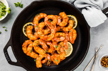 Overhead shot of Easy Cajun Honey Butter Shrimp garnished with slices of lemon in a small cast iron skillet with seafood forks, a neutral colored linen and ramekin of microgreens arranged around the skillet.