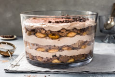 Slightly angled, straight on shot of an Easy Chocolate Tiramisu Trifle on a pale blue linen with a mini fine mesh sifter full of cocoa powder off to the side of the trifle and a small ramekin of shaved chocolate and small glass containing spoons blurred behind the trifle.