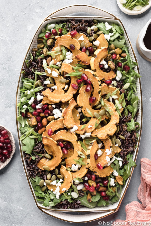 Overhead shot of Roasted Delicata Squash Wild Rice Salad garnished with pomegranate arils and sliced scallions on a white platter with ramekins of pomegranate arils, sliced scallions and a small container of honey balsamic vinaigrette arranged around the salad.