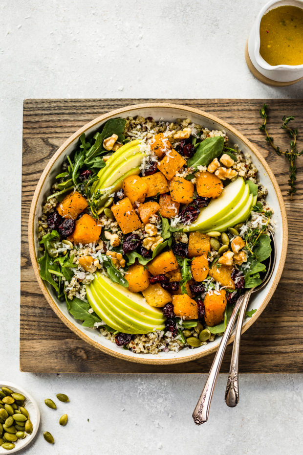Overhead shot of Fall Butternut Squash Quinoa Salad in a neutral colored bowl on a wood board with two spoons inserted into the salad; and a small ramekin of apple cider vinaigrette and ramekin of pepitas arranged around the board.