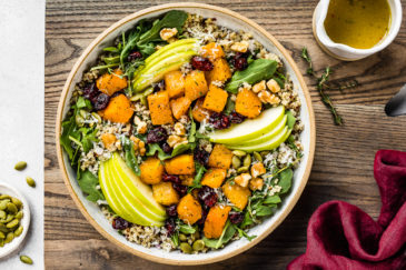 Overhead shot of Fall Butternut Squash Quinoa Salad in a neutral colored bowl on a wood board with a small ramekin of apple cider vinaigrette, dark red linen and ramekin of pepitas arranged around the board.