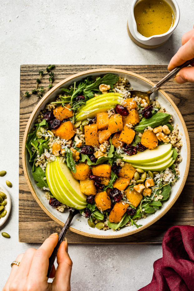 Overhead shot of Fall Butternut Squash Quinoa Salad in a neutral colored bowl on a wood board with two hands holding serving spoons tossing the salad; and a small ramekin of apple cider vinaigrette, a dark red linen and ramekin of pepitas arranged around the board.