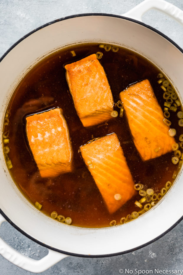 Overhead shot of a large pot filled with green tea poaching liquid and salmon filets - photo of step 4 of the Green Tea Poached Salmon Soba Noodles recipe.