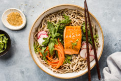 Overhead shot of Green Tea Poached Salmon Soba Noodles with arugula, sliced radishes and julienned carrots in a neutral colored bowl with chopsticks resting on the edge; and a ramekin of sesame seeds, sliced scallions and a pale blue linen arranged around the bowl.