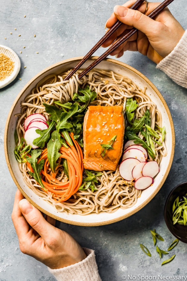 Overhead shot of Green Tea Poached Salmon Soba Noodles with arugula, sliced radishes and julienned carrots in a neutral colored bowl with a hand holding chopsticks inserted into the noodles and another hand resting on the side of the bowl; with a ramekin of sliced scallions and sesame seeds arranged around the bowl.
