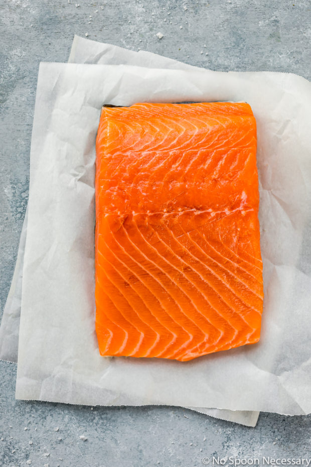 Overhead shot of a large center-cut salmon filet with pin bones removed on two layered pieces of white parchment paper - photo of the main ingredient in the Green Tea Poached Salmon Soba Noodles recipe.